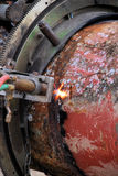 Acetylene torch and iron pipe. An acetylene torch cutting a pipe.  The flame splashes out from the groove where the pipe is being cut Royalty Free Stock Photos