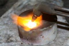 Acetylenfackel, die unten heiße Edelmetalle schmilzt Stockfotos