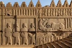 Achaemenid Bas Relief Carvings do combate do leão e da Bull ao lado dos soldados em Persepolis Imagens de Stock Royalty Free