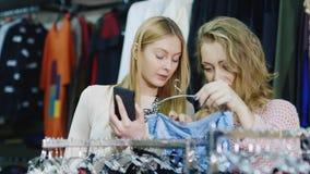 Achat avec le smartphone Deux femmes regardent des choses dans un magasin d'habillement, utilisent le téléphone banque de vidéos