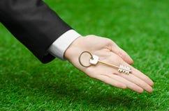 Achat d'une nouvelle maison ou d'une terre et d'un sujet d'affaires : main dans un costume noir tenant une clé sur la nouvelle ma Photographie stock