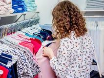 Achat dans le magasin de mode La fille choisit des vêtements dans un tre image libre de droits