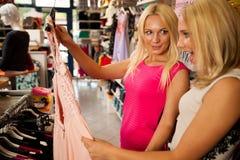 Achat dans le magasin de vêtements - deux femmes mignonnes dans la boutique d'habillement sélectionnent Images libres de droits