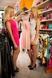 Achat dans le magasin de vêtements - deux femmes mignonnes dans la boutique d'habillement sélectionnent Photo libre de droits