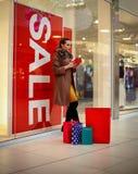 Achat - jeune femme de sourire dépensant l'argent pour l'achat durée Photo stock