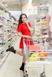 Achats étonnés de femme au supermarché Photographie stock libre de droits