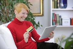 Achats aînés de femme en ligne Photo stock