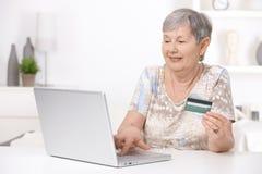 Achats aînés de femme sur l'Internet Image libre de droits