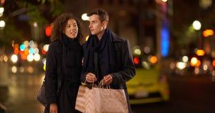 Achats avec du charme de couples la nuit dans la grande ville Photographie stock libre de droits