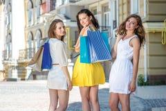 Achats communs Trois filles tenant des paniers et l'arou de promenade Photo stock
