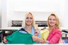 Achats d'achats de femme de deux blondes adaptant la robe colorée, boutique de sourire heureuse de mode de clientes de filles cho Image stock