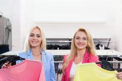 Achats d'achats de femme de deux blondes adaptant la robe colorée, boutique de sourire heureuse de mode de clientes de filles cho Photographie stock libre de droits