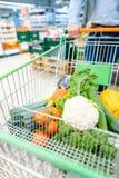Achats d'homme dans le supermarché poussant son chariot avec des légumes photo libre de droits