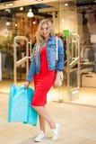 Achats de concept Le portrait de la femme de sourire blonde de beauté dans des paniers se tenants occasionnels près font des empl photo libre de droits