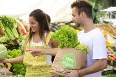 Achats de couples au marché en plein air ouvert. Photo libre de droits