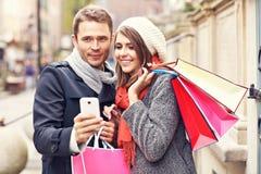 Achats de couples dans la ville avec le smartphone Photos libres de droits