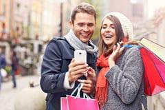 Achats de couples dans la ville avec le smartphone Images libres de droits