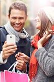 Achats de couples dans la ville avec le smartphone Photo libre de droits