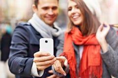 Achats de couples dans la ville avec le smartphone Image libre de droits