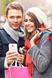 Achats de couples dans la ville avec le smartphone Photo stock