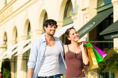 Achats de couples et argent de dépenses dans la ville Images stock
