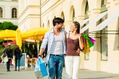 Achats de couples et argent de dépenses dans la ville Photo stock