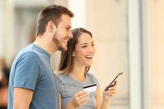 Achats de couples sur la ligne observant un devanture de magasin Photo libre de droits