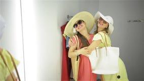 Achats de deux femmes essayant les robes dr?les pr?s du miroir Beaux jeunes clients dans la cabine d'essayage banque de vidéos