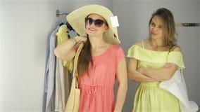 Achats de deux femmes essayant un chapeau dr?le avec des lunettes de soleil Beaux jeunes clients dans la cabine d'essayage clips vidéos