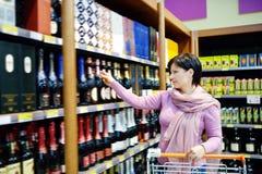 Achats de femme et boisson alcoolisée de choix au supermarché Photographie stock libre de droits