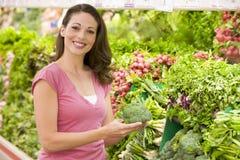 Achats de femme pour des légumes dans le supermarché Image libre de droits