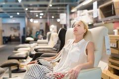 Achats de femme pour la nouvelle chaise de basculage dans le magasin de meubles Photographie stock