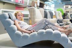 Achats de femme pour la nouvelle chaise de sofa dans le magasin de meubles Images stock