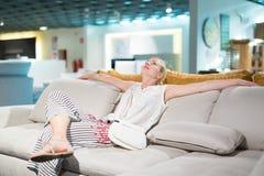 Achats de femme pour le nouveau sofa dans le magasin de meubles Photographie stock