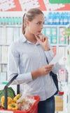 Achats de jeune femme au supermarché Image libre de droits