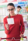 Achats de jeune femme au supermarché Photo stock