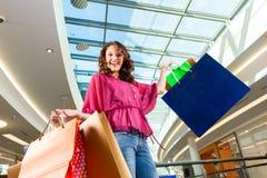 Achats de jeune femme dans le mail avec des sacs Photo stock