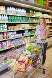 Achats de jeune femme et marchandises de choix au supermarché images libres de droits