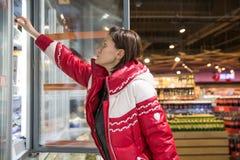 Achats de jeune femme pour les produits fondus dans une épicerie Libre service image stock