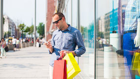 Achats de jeune homme dans le mail avec beaucoup de paniers colorés dans sa main. Il tient un téléphone. Images stock