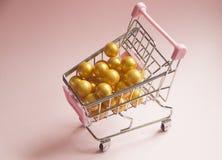 achats de l'image 3d produits par chariot Chariot à supermarché complètement des boules d'or sur le fond rose Photo de concept de Photographie stock