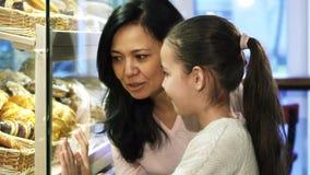 Achats de mère et de fille à la boulangerie choisissant la pâtisserie dans l'étalage banque de vidéos