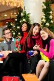 Achats de Noël d'amis avec des présents dans le mail Photo stock