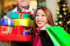 Achats de Noël de couples avec des présents dans le mail Photos stock