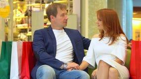Achats de Noël, idée pour votre conception Le couple se repose sur un sofa au centre commercial Paquets des achats Grands paquets banque de vidéos
