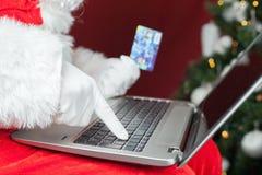 Achats de Santa par le cadeau en plastique de Noël de carte dans l'Internet Image libre de droits