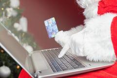 Achats de Santa par le cadeau en plastique de Noël de carte dans l'Internet Photo libre de droits