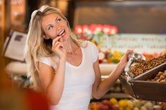 Achats de sourire de femme dans le supermarché photo stock