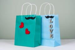 Achats de vacances, cadeaux Les paniers avec des lettres et des coeurs d'amour couplent le homme-homme Photographie stock libre de droits