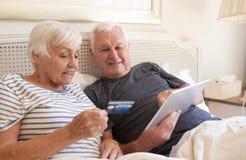 Achats en ligne d'aînés avec un comprimé numérique dans le lit Image stock
